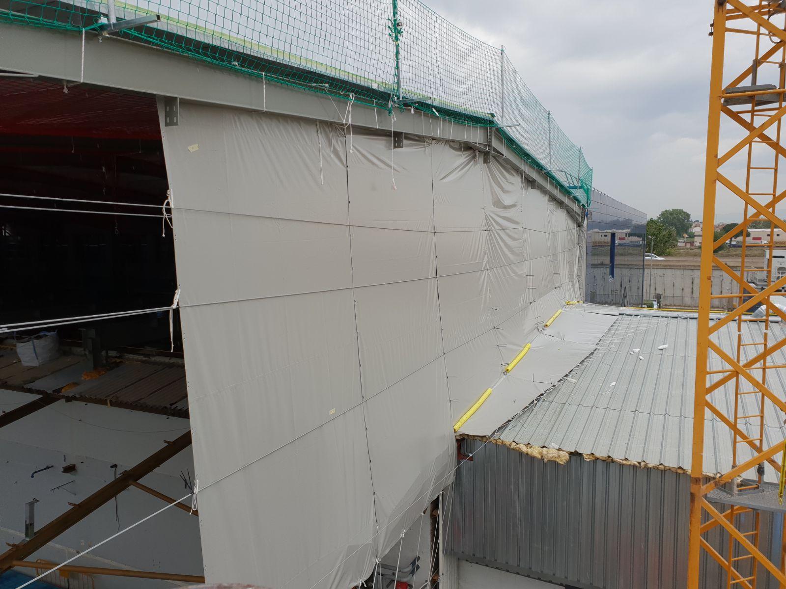 Coberta provisional del lateral d'una nau per poder retirar el sostre i evitar l'entrada d'aigua.